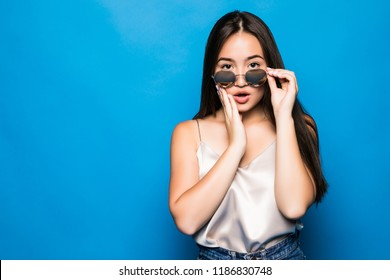 Young Asian woman with surprise pose isolated on blue background. Portrait of beautiful Asian woman with pink sunglasses posing surprise gesture for shock, freak, fear, fright concepts.