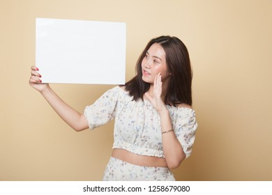 Young Asian woman  surprise with  white blank sign on beige background