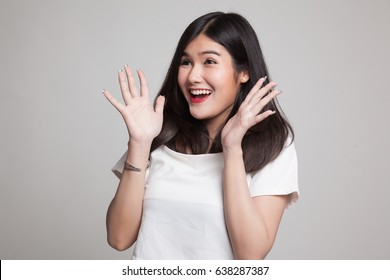 Young Asian woman is surprised and smile on gray background