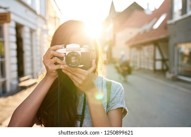 Young Asian woman taking photographs with a vintage slr camera while walking around the city in the afternoon