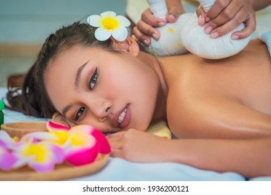 Young Asian woman is taking Thai Herbal ball hot compress massage in an authetic spa authentic