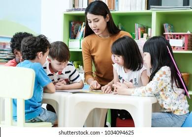 Young asian woman teacher teaching kids in kindergarten classroom, preschool education concept