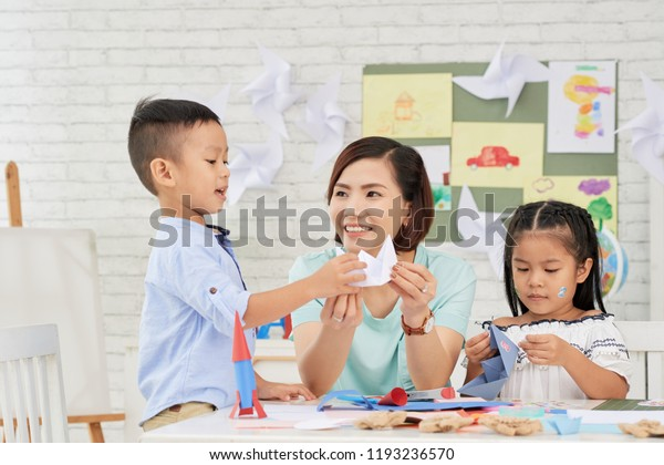 Young Asian woman teaching children how to make paper ships at art craft