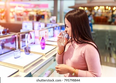 Young asian woman testing and choose to buy perfume in duty free store at international airport.