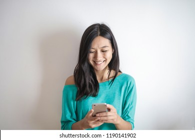 Young Asian woman texting.