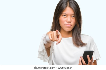 Young asian woman texting using smartphone over isolated background pointing with finger to the camera and to you, hand sign, positive and confident gesture from the front