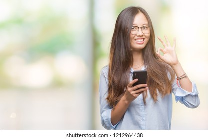 Young asian woman texting using smartphone over isolated background doing ok sign with fingers, excellent symbol