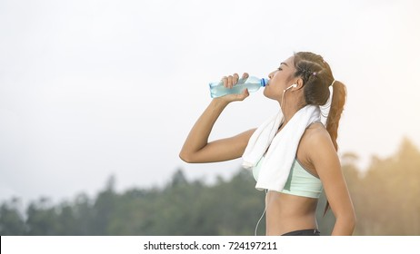 young asian woman thirsty and drinking pure water after jogging or exercise healthily concept