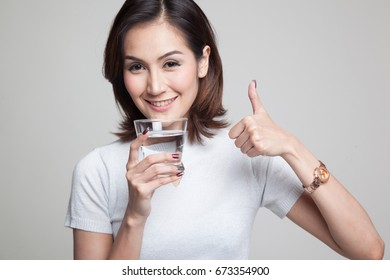 Young Asian woman thumbs up with a glass of drinking water on gray background