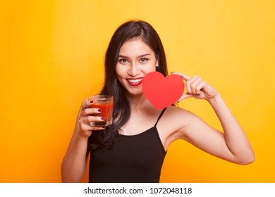 Young Asian woman with tomato juice and red heart on yellow background