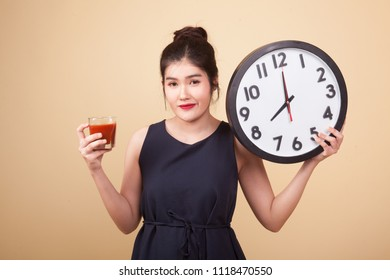 Young Asian woman with tomato juice and clock  on beige background