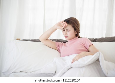 Young asian woman  touching her forehead on the bed. Woman sick concepts : headache, dizziness, fever.