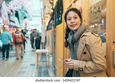 Young asian woman tourist in coat browsing internet website on mobile phone and looking aside on street in local market. girl leaning on wall of izakaya restaurant waiting for friend smiling.
