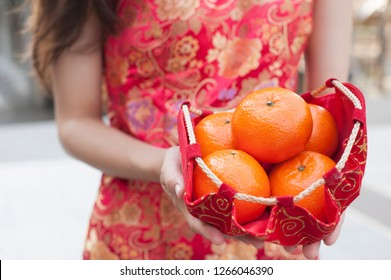 Young Asian woman in traditional chinese red dress holding fresh oranges in red silk fabric basket. Happy Chinese New Year concept.