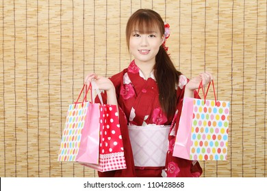Young asian woman in traditional clothes of kimono with shopping bag