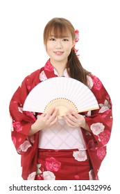 Young asian woman in traditional clothes of kimono holding paper fan