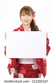 Young asian woman in traditional clothes of kimono holding a blank white board