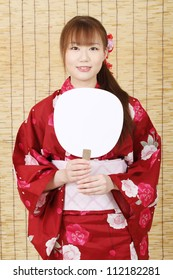 Young asian woman in traditional clothes of kimono with paper fan