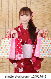 Young asian woman in traditional clothes of kimono with shopping bags