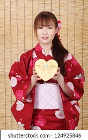Young asian woman in traditional clothes of kimono, holding a gift box
