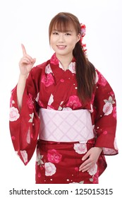 Young asian woman in traditional clothes of kimono, pointing up