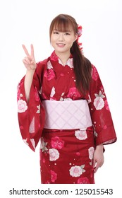 Young asian woman in traditional clothes of kimono with peace sign