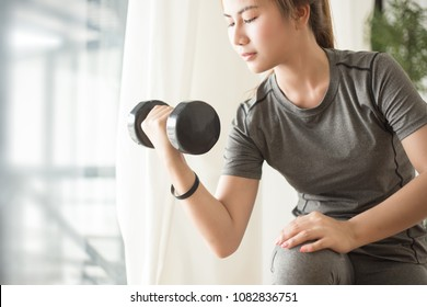 Young asian woman training with dumbell at home. Fitness and healthy lifestyle concept