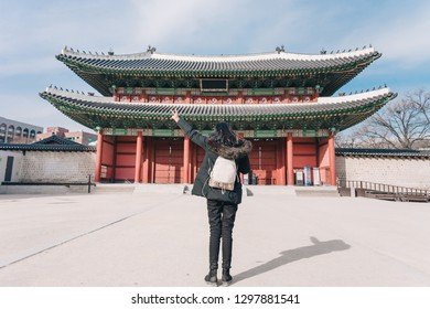 Young asian woman traveler with backpack traveling into the Deoksugung Palace's Daehanmun Gate at Seoul city, South Korea.