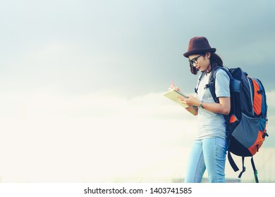 Young asian woman traveler with backpack writing note about her travel memory,Travel concept.