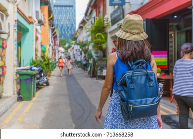 Young asian woman traveler with backpack and hat walking at Haji Lane - Bali Lane in Singapore city downtown, Traveling in Singapore.