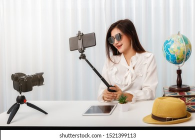 Young asian woman traveler blogger selfie herself with smart phone while recording vlog video live streaming. blogger and vlogger online influencer on social media concept.
