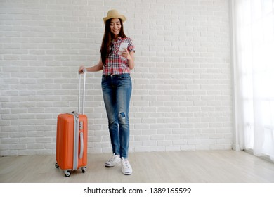 Young asian woman traveler holding smart phone and  luggage in white room with copy space, people summer holiday vacation background concept