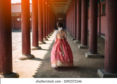 Young asian woman traveler in korean national dress or Hanbok walking traveling into the Gyeongbokgung Palace at Seoul city, South Korea.