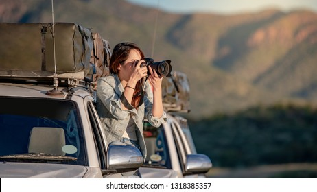 Young Asian woman traveler and photographer sitting on the car window taking photo on road trip in Namibia, Africa. Travel photography concept