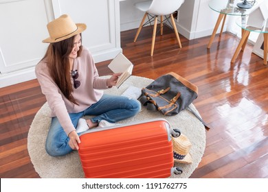 Young asian woman traveler prepare things into orange suitcase for holiday vacation at home.backpacker travel concept