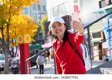 Young asian woman traveler selfie by cellphone in Hongdae(Hongik University) shopping street. Hongdae is a shopping cultural street for young people in Seoul.