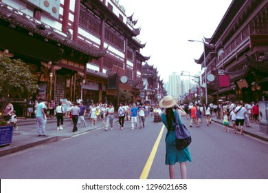 Young asian woman traveler traveling and taking photo at chinatown shopping street in China