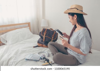 Young asian woman traveller planning vacation holiday expedition and booking ticket and hotel online with mobile phone app on bed.preparing to travel.digital lifestyle