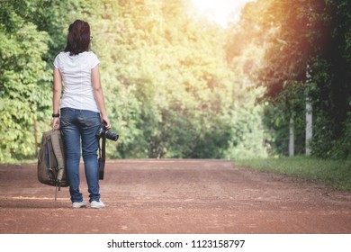 young asian woman traveller walking into the woods.