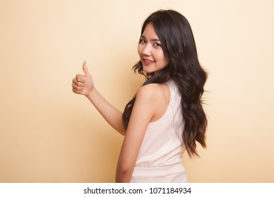 Young Asian woman turn back thumbs up  on beige background