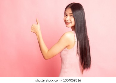 Young Asian woman turn back thumbs up on pink background