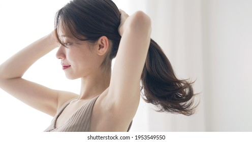 Young asian woman tying her hair. Hair care. Beauty concept.