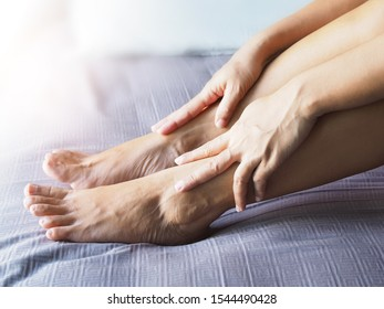 Young asian woman use hand massage on leg to relieve ankle pain.