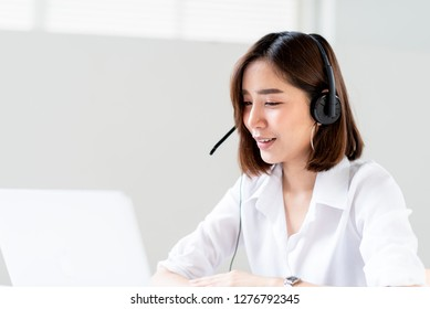 Young Asian woman use a headset for tele communication meeting in an office