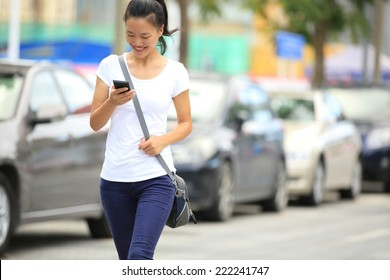 young asian woman use her cellphone walking at parking lot