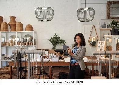 Junge Asiatische Frauen, die eine digitale Tablette benutzen, während sie in ihrer stilvollen Boutique an einem Display stehen