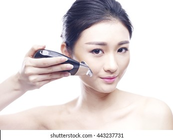 young asian woman using a face spa instrument, isolated on white.