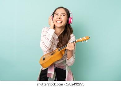 Junge asiatische Frau, die Kopfhörer benutzt, während sie mit glücklicher Ukulele spielt. Menschen Lifestyle-Konzept.