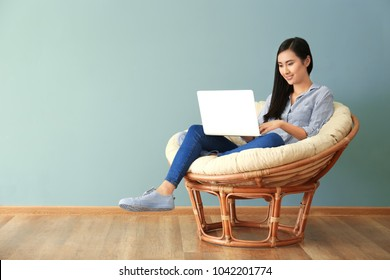 Young Asian woman using laptop in lounge chair, indoors