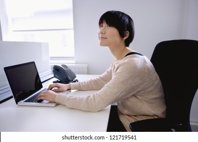 Young Asian woman using laptop while looking away